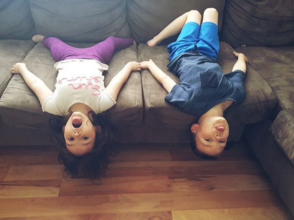 two kids hanging upside down on the sofa