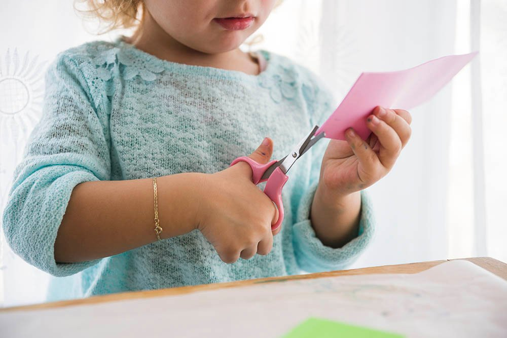 Example of bilateral coordination - a girl cutting a piece of paper with scissors.