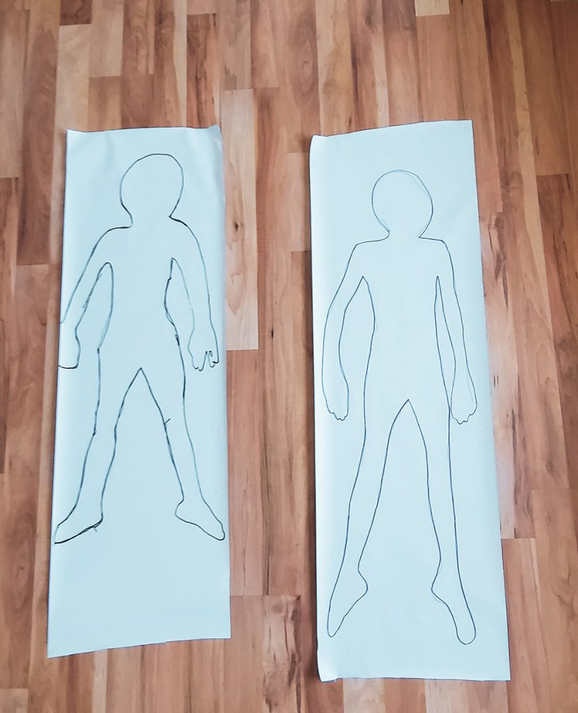 outline of kids bodies on paper for body check chart.
