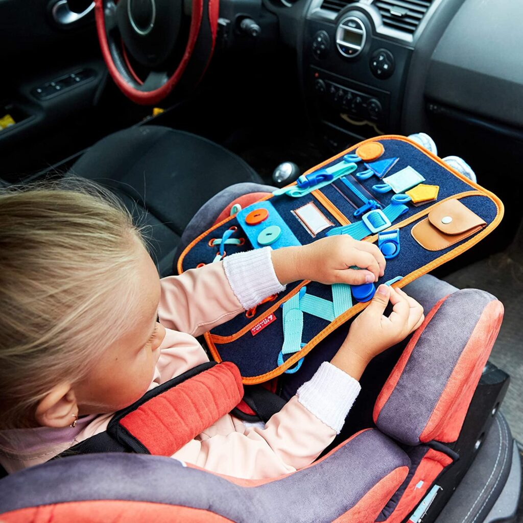 child in car using learning backpack to practice fine motor skills.